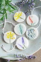 Decorated salt dough tiles with string for hanging arranged on a plate.