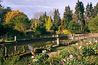 View of formal pond surrounded by borders showing seasonal colour.