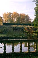 View over formal pond surrounded by borders showing seasonal colour.
