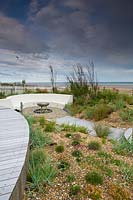 Modern, landscaped seaside garden, with curved bench and gravel borders.