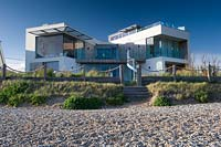 View of modern, glass seaside house from the beach.