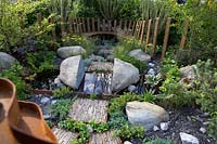 Through Your Eyes Garden. Wooden seating area with slate pieces inlaid into corten steel frames to form stepping stones. Water pool with 'split' rock.   Planting includes Deschampsia cespitosa, Achillea 'Moonshine', Ophiopogon planiscapus 'Nigrescens' - Sponsors: Kebony, CED Stone, R and G Metal Products, William's Art and Design, Practicality Brown.