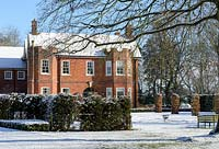 Period red brick house with Carpinus betulus - Hornbeam pillars, Taxus baccata - yew hedge, branches of Fagus sylvatica f. purpurea - large copper beech. Snow in January.