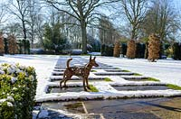 Sculpture of terrier by Harriet Mead, made from reclaimed metal machinery. Carpinus betulus - Hornbeam pillars, Taxus baccatta - yew hedge with stone paving and Fagus sylvatica f. purpurea - large copper beech.  Buxus - box hedging. Snow in January.