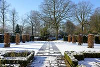 Carpinus betulus - Hornbeam pillars, Taxus baccatta - yew hedge with stone paving and Fagus sylvatica f. purpurea - large copper beech.  Buxus - box hedging with roses. Snow in January.