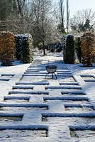 Carpinus betulus - Hornbeam pillars, Taxus baccata - yew hedge with stone paving and small metal fire pit. Snow in January.