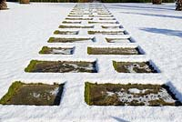 Stone paving across the lawn with snow in January.