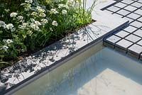 Water rill with square pavers, border with white perennial planting. RHS Hampton Court Palace Flower Festival 2019.