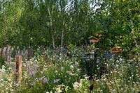 Bistro table and chairs set in a wildflower meadow, surrounded with birch trees and habitat houses. RHS Hampton Court Palace Flower Festival 2019.