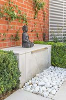 Water feature with sheet of water falling onto pebbles and buddha statue.
