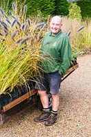 Nurseryman next to ornamental grasses ready for sale