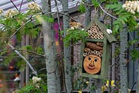 The Montessori Centerary Children's Garden. Bug hotel hanging in the branches of Sorbus aucuparia - Common Rowan. Sponsors: Montessori Centre International  and  City Asset Management