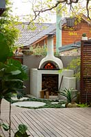 A bespoke cement rendered pizza oven in the back corner of a backyard showing a slat hardwood timber screen and a timber deck.