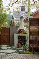 A bespoke cement rendered pizza oven in the back corner of a backyard.