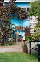 Detail view of a light blue painted cottage with a display of hand made pottery objects with a purple leaved Vitis vinifera, Ornamental grape vine growing over it featuring a glossy black painted metal garden bench.