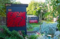 Decorative red painted metal panel with oak leaf and acorn motif mounted onto the wall of a grey painted outhouse in a backyard in front of a garden shed with a red metal garden bench.