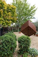 A rusty metal cube sculpture with a pattern of holes cut into sitting in the middle of a pebble mulched garden featuring a low clipped hedge.
