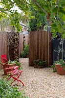 View of a pebble mulched garden with bright red metal garden chairs, potted plants, a side gate and featuring a Ginkgo biloba, tree.