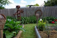 A human like figure made from rusty metal next to handmade pottery garden stake topper of a stylised face in the corner of a timber edged raised garden beds in front of a rusty steel wall decoration.