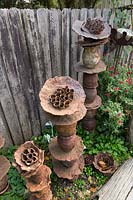 Overhead deatail of a group of organic shaped pottery towers in front of a timber paling fence in a garden bed.