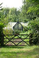 Classic greenhouse in the kitchen garden with gate.