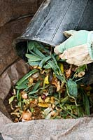 Emptying compostable kitchen waste into a compost bin
