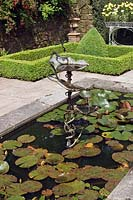 Metal water feature in a small formal pond in a courtyard with clipped buxus bed