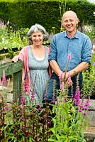 Couple standing by plant sales area in a nursery