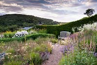 View over prairie-style planting a bench backed by a hedge, wooded hills beyond. Plants include: Molinia caerulea subsp. caerulea 'Poul Petersen', Achillea, Hordeum jubatum 'Early Pink' and Calamintha nepeta subsp. nepeta 'Blue Cloud' with white Erigeron annuus