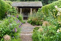 The herb garden with clipped yew spheres around a central circle set with a mill stone, and lush planting including fennel, alliums and verbena with slate roofed summerhouse at the end in July. York Gate Garden, Adel.