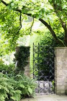 Elegant wrought iron gate of squares and circles at York Gate garden, Adel in July.