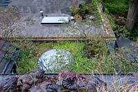 View over balcony planter of grasses and Heuchera down to garden.