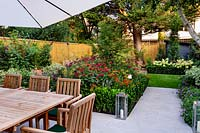 Stone patio area in West London garden, with wooden table, chairs and parasol. In the background there is a border featuring Monarda Fire Ball, Acer palmatum, Helenium Moerheim Beauty, Euonymus Jean Hughes.