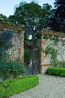 Brick walled garden with open wooden gateway.