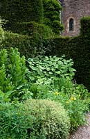 Corner of a full mixed border backed by hedging