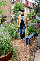 Modern cottage garden in West London. Owner and garden designer Nick Gough walking through garden with watering can.