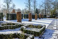 Carpinus betulus - Hornbeam pillars, Taxus baccata - yew hedge with stone paving and Buxus - box hedging with roses. Snow in January.