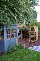 Contemporary garden in Wimbledon - with children's play area with climbing frame and shed.