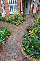 A Spring front garden in West London with a brick path leading to the house