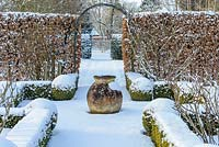 The Potager with Buxus - box hedging and topiary shapes. Fagus - Beech hedge and  terracotta oil jar with a covering of snow. The Old Rectory, Suffolk UK