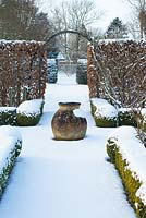 The Potager with Buxus - box hedging and topiary shapes. Fagus - Beech hedge and  terracotta oil jar with a covering of snow. The Old Rectory, Suffolk, UK