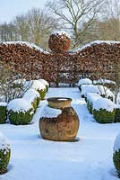 The Potager with Buxus - box hedging and topiary shapes. Fagus - Beech hedge with topiary ball and  terracotta oil jar with a covering of snow. The Old Rectory, Sufolk, UK
