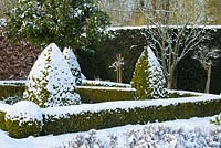 The Potager with Buxus - box hedging and topiary shapes, Fagus - Beech hedge and Taxus baccata - yew hedge. Large Laurus nobilis - standard Bay tree with a covering of snow. The Old Rectory, Suffolk, UK