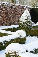 The Potager with Buxus - box hedging and topiary shapes, Fagus - Beech hedge and Taxus baccata - yew hedge with a covering of snow in late February. The Old Rectory, Suffolk, UK