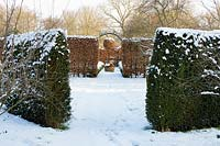 The Potager with Fagus - Beech hedges with a topiary ball and  terracotta oil jar, Taxus baccata hedges in the foreground with a covering of snow in late February. The Old Rectory, Suffolk, UK