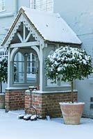 Pair of terracotta pots with Laurus nobilis - standard Bay trees by Wooden and brick porch with boot scraper and brushes, snow in February. The Old Rectory, Suffolk, UK