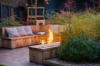 Seating area with fire pit and round wooden bench surrounded by Miscanthus sinensis 'Morning Light' - eulalia and Erysimum 'Bowles's Mauve'