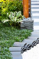 Detail of a curved path edged with traditional curved Chinsese roof tiles,  mulched with white quartz pebbles, the garden is planted with dwarf Mondo Grass with a variegated Hosta.