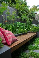 A cement rendered planter box with a hardwood timber inbuilt bench seat with two red patterned cushions, planted with Baby Panda Grass and a flowering Gardenia.