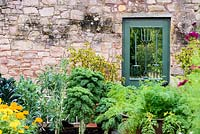 A door into the Walled Garden incorporating old hand forks at Broadwoodside, Gifford, East Lothian, Scotland